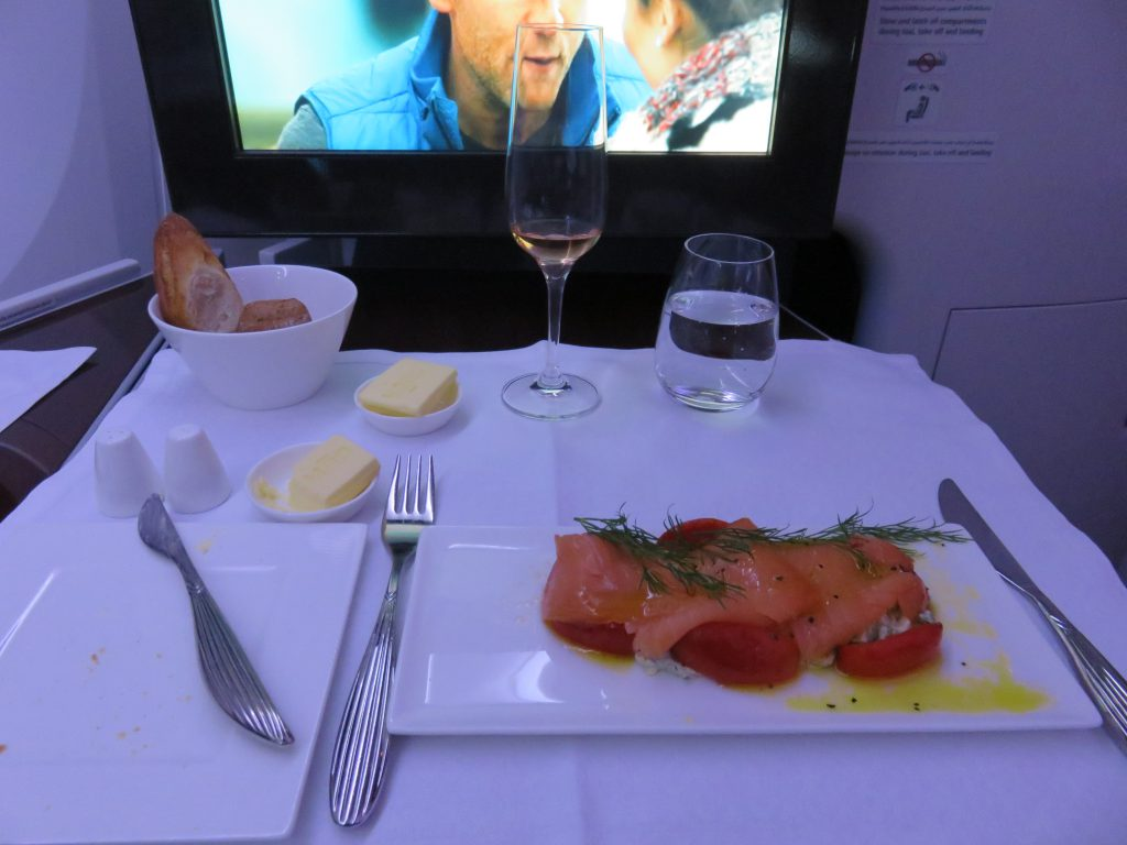 a picture of my meal on board the plane with a movie on the screen