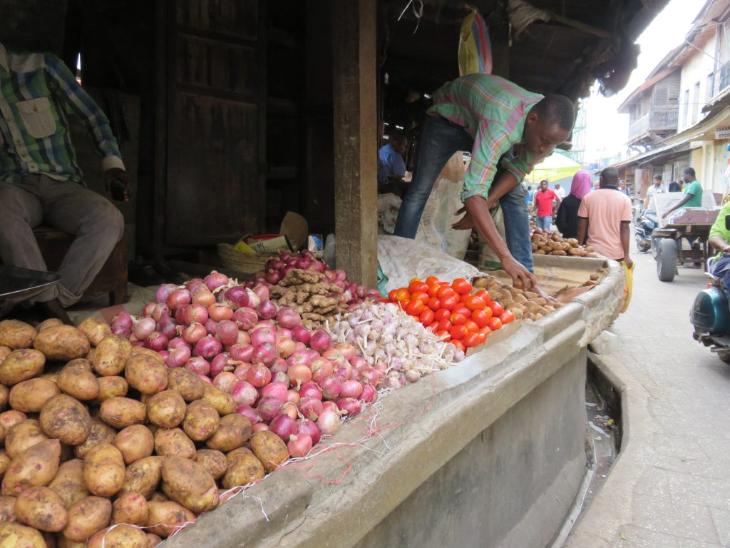 vegetable seller arranging his stall