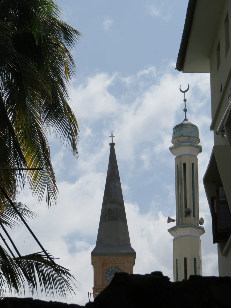 tower of a church and a mosque side by side
