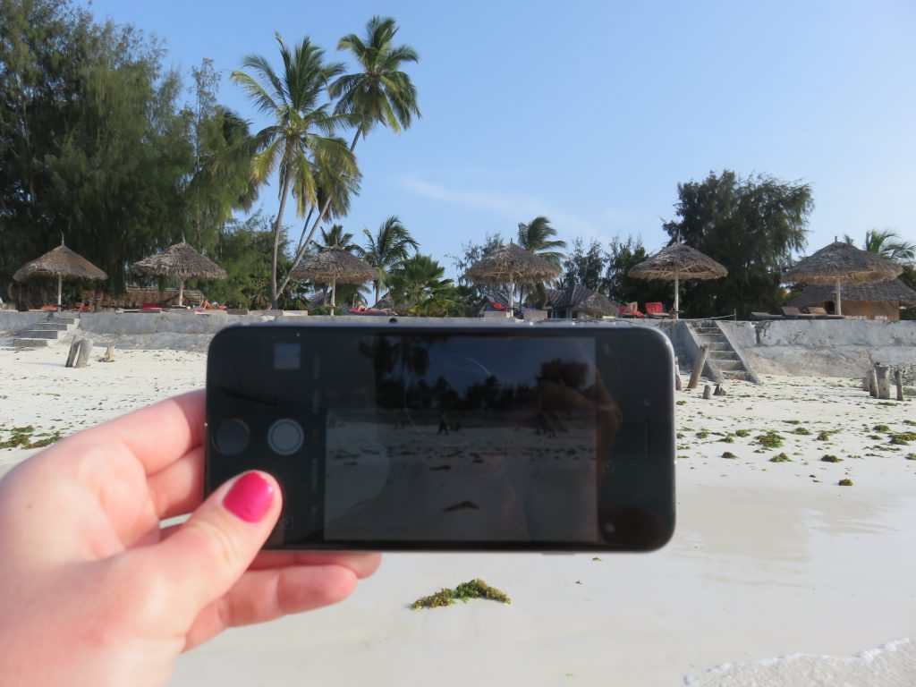 Me taking a photo of a beach with my iPhone
