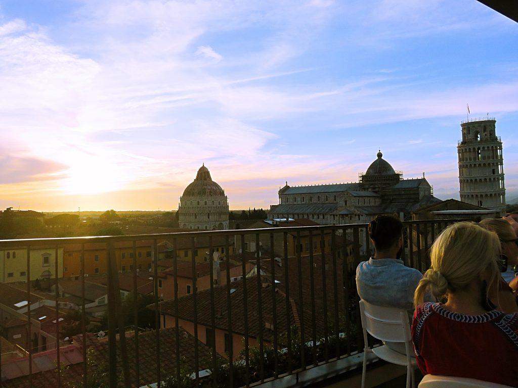 a picture of tourists at sunset enjoying the view from the rooftop restaurant
