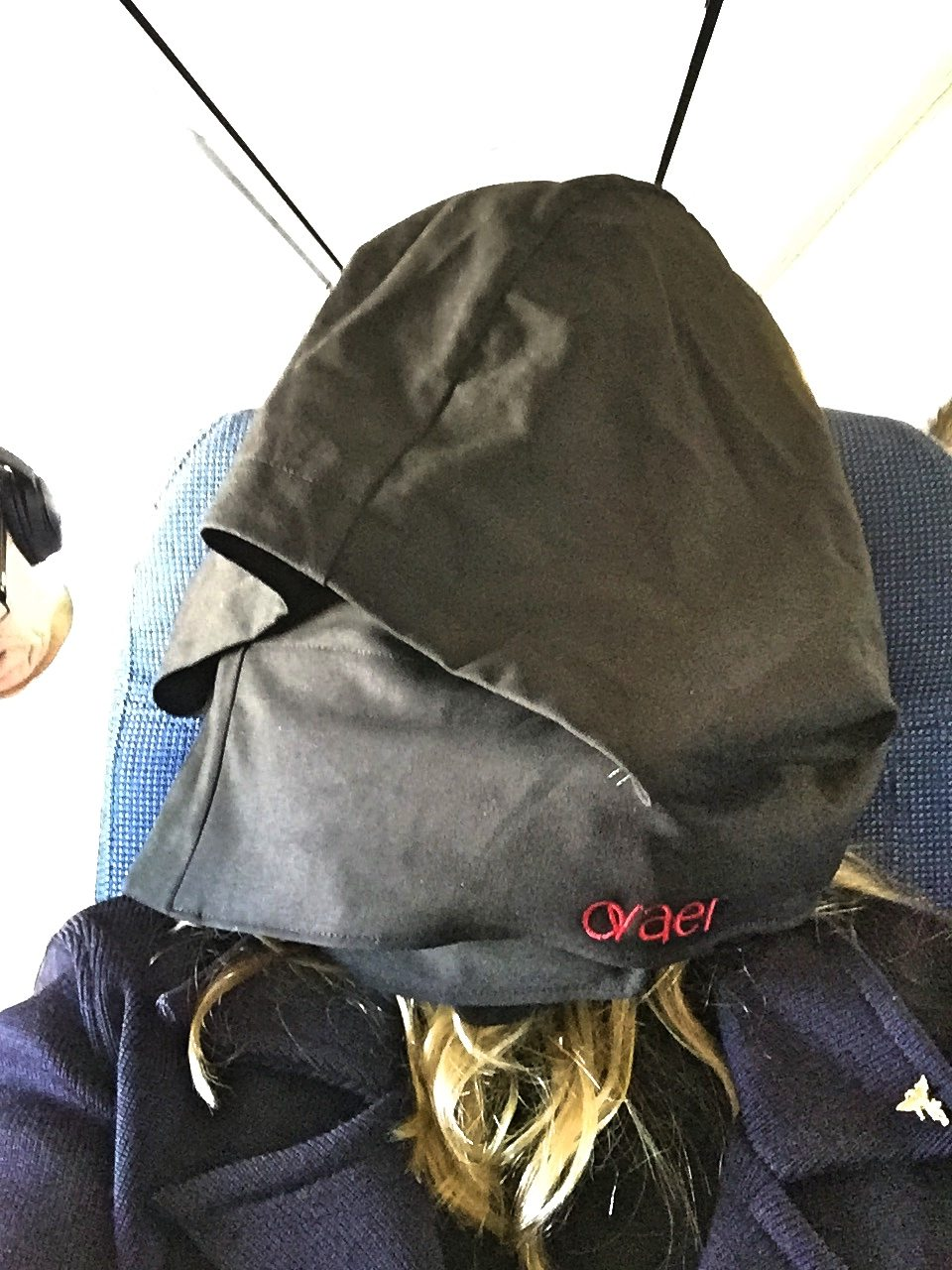 A picture of me wearing the neck pillow and hoodie and completely covering my face
