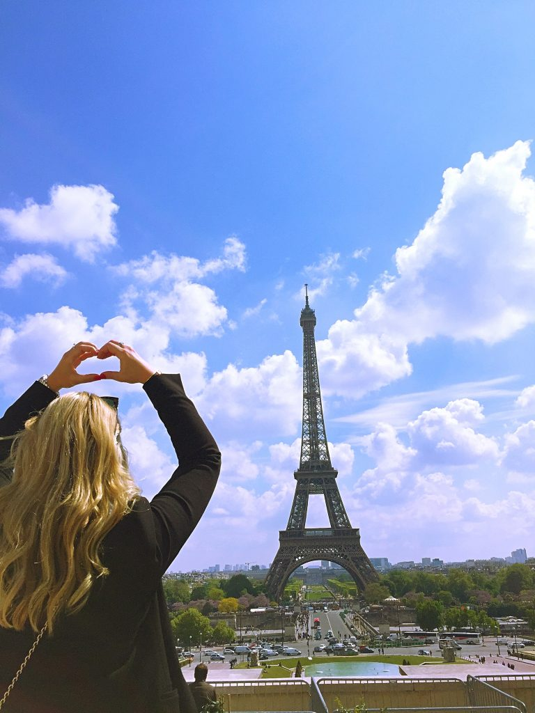 A picture of me posing at the Eiffel tower in Paris