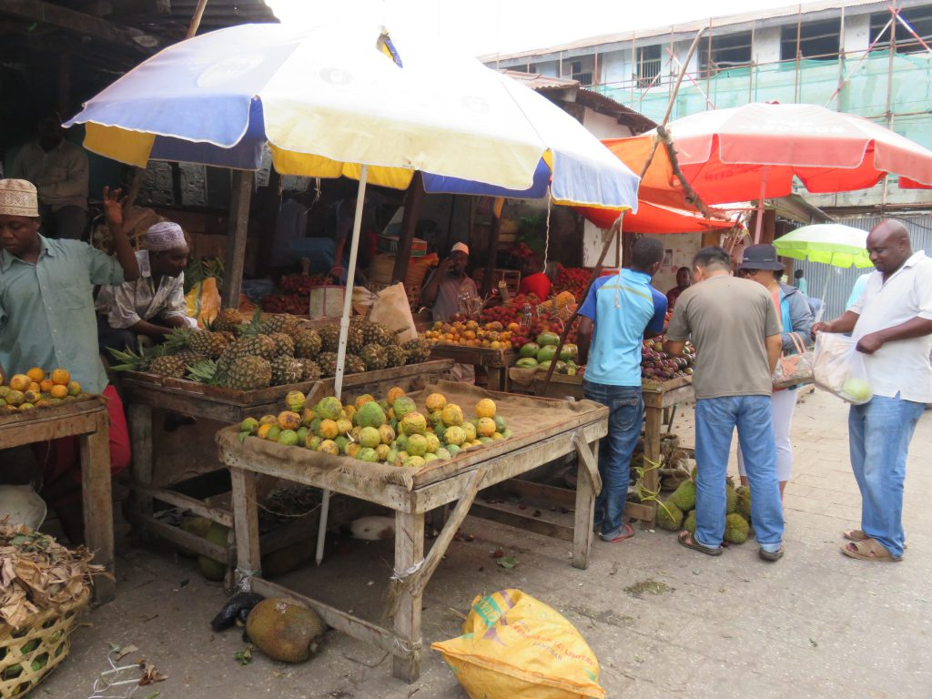 people buying fruits at a fruit stall