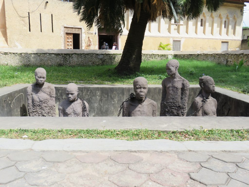 a sculpture depicting slaves on display for auction