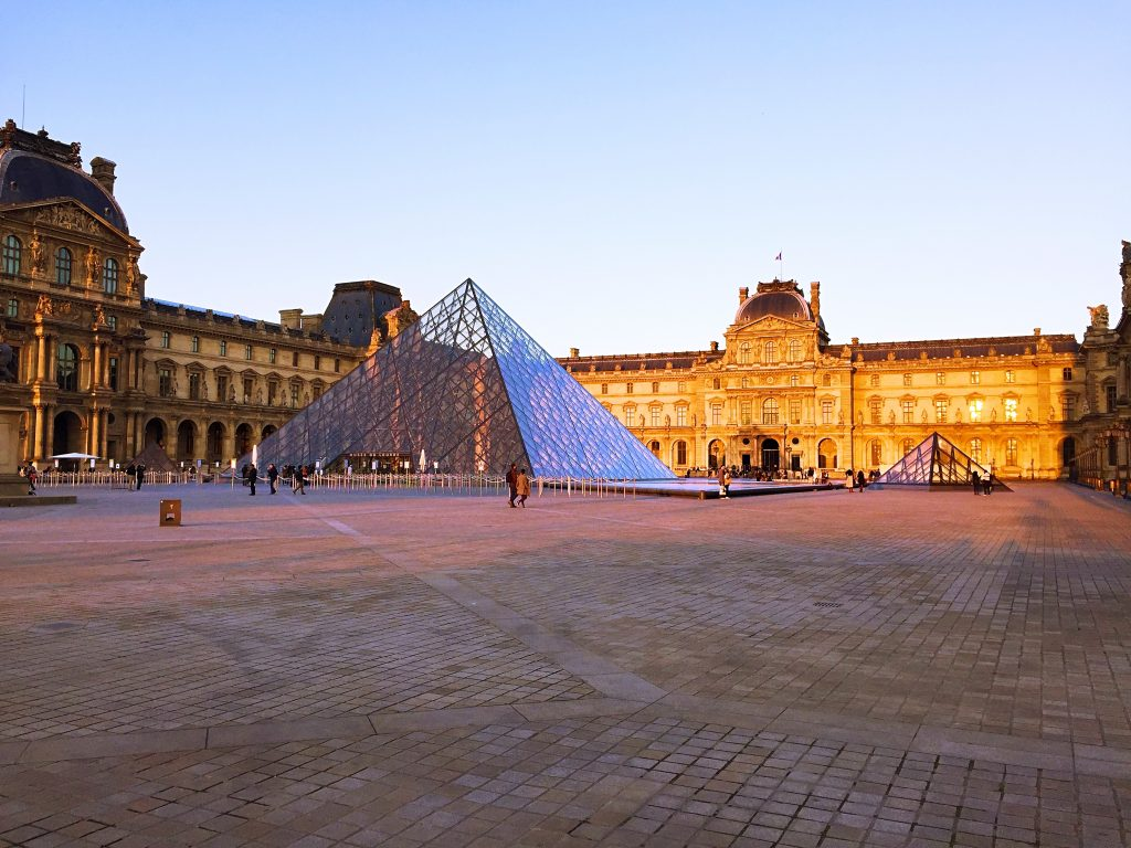 a picture of the square and glass pyramid at the Louvre