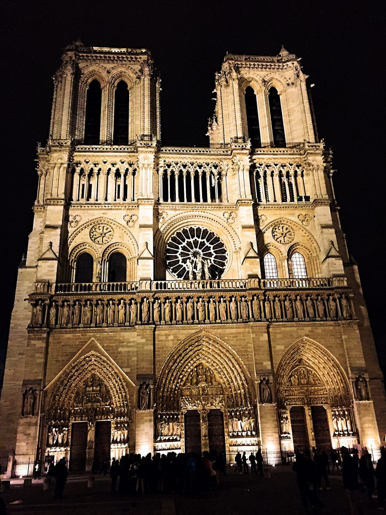 a picture of the entrance of Notre Dame at night
