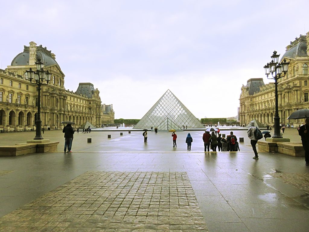a picture of tourists outside the glass pyramid at the louvre