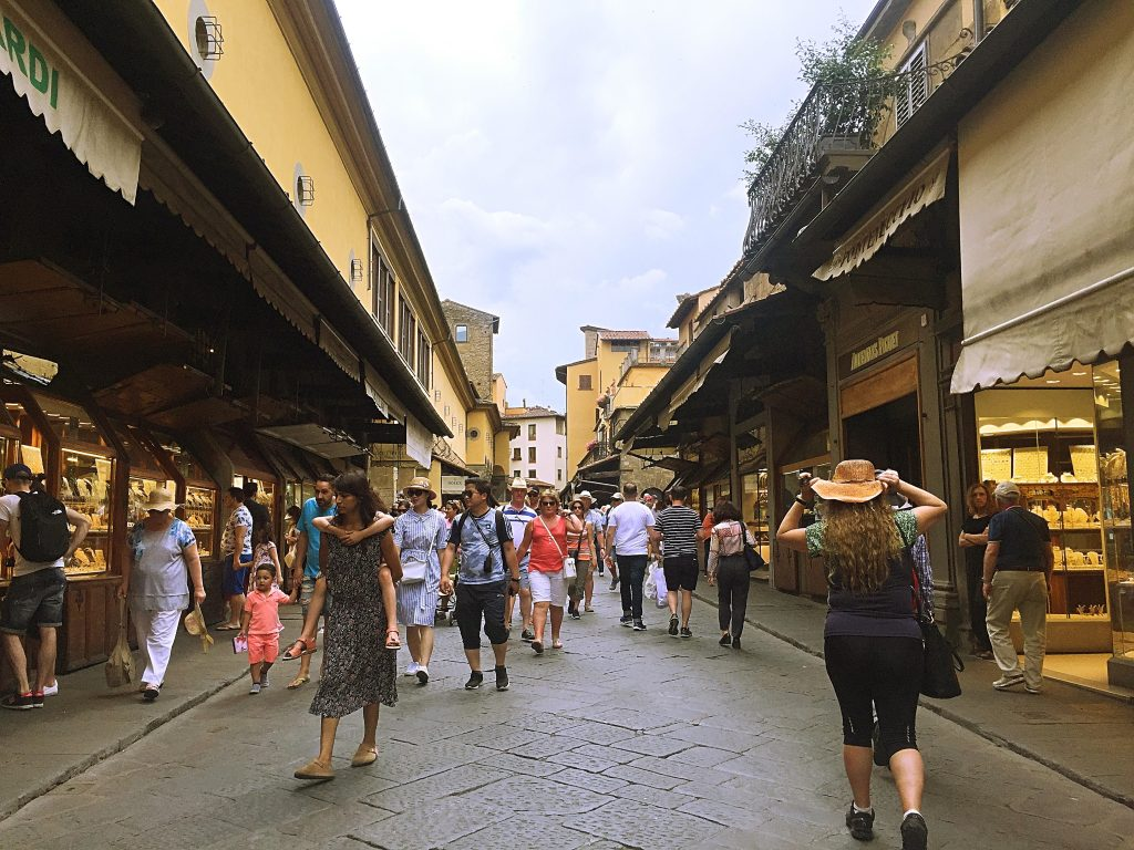 A picture of tourists walking along the street shopping