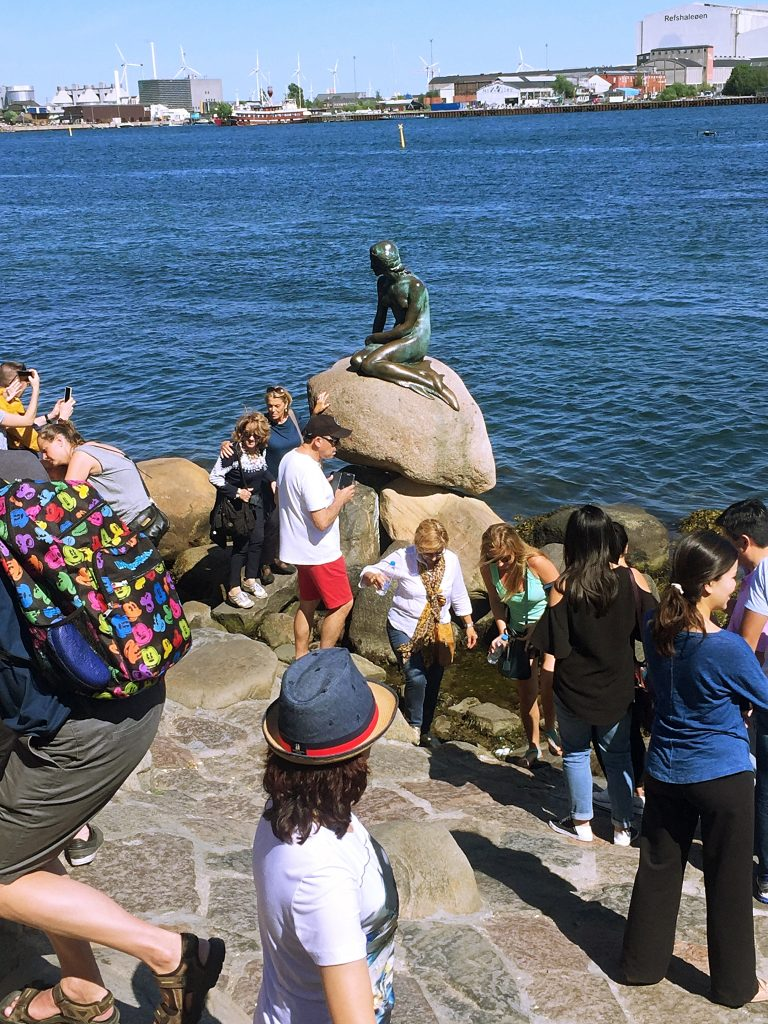 Tourists waiting in line to take pictures with the little mermaid sculpture