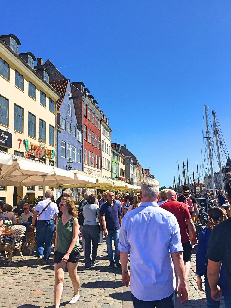 A picture of tourists walking in an area called Nyhavn