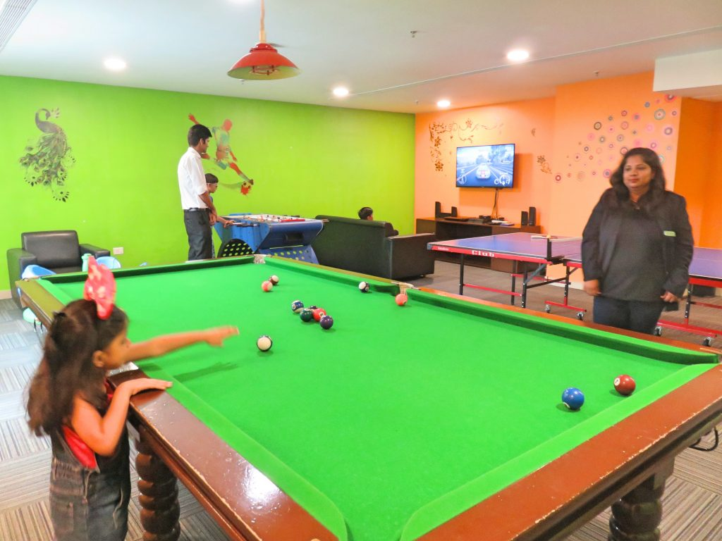 A picture of games room with a pool table video games and table tennis
