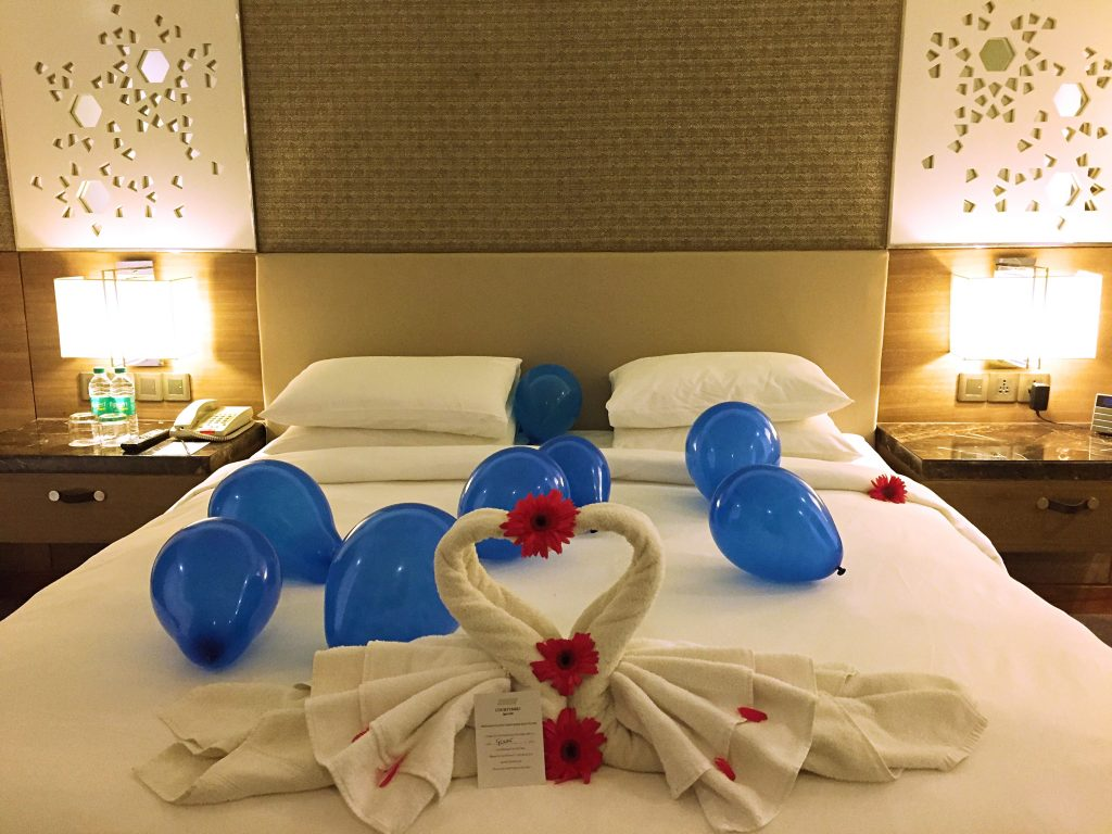 A picture of balloons and towel filed in the shape of swans by housekeeping